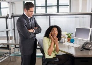 Boss catching businesswoman using cell phone