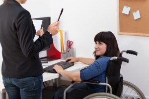 Disabled woman on wheelchair talking with manager